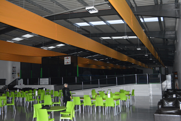 textile duct deflated above seating area with tables at trampoline park