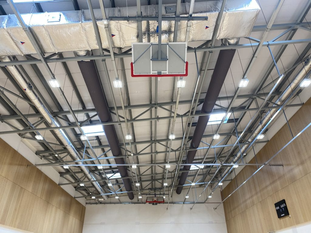 Dark grey exposed ductwork installed through structural steelwork in a sports hall