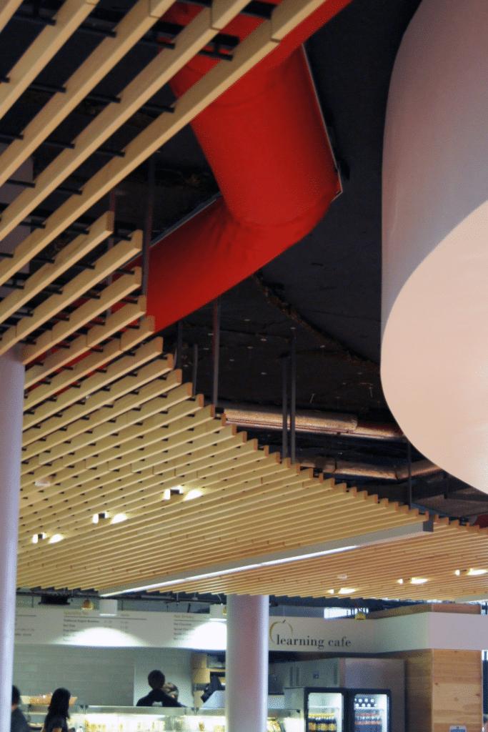 Red fabric duct peeking through ceiling slats