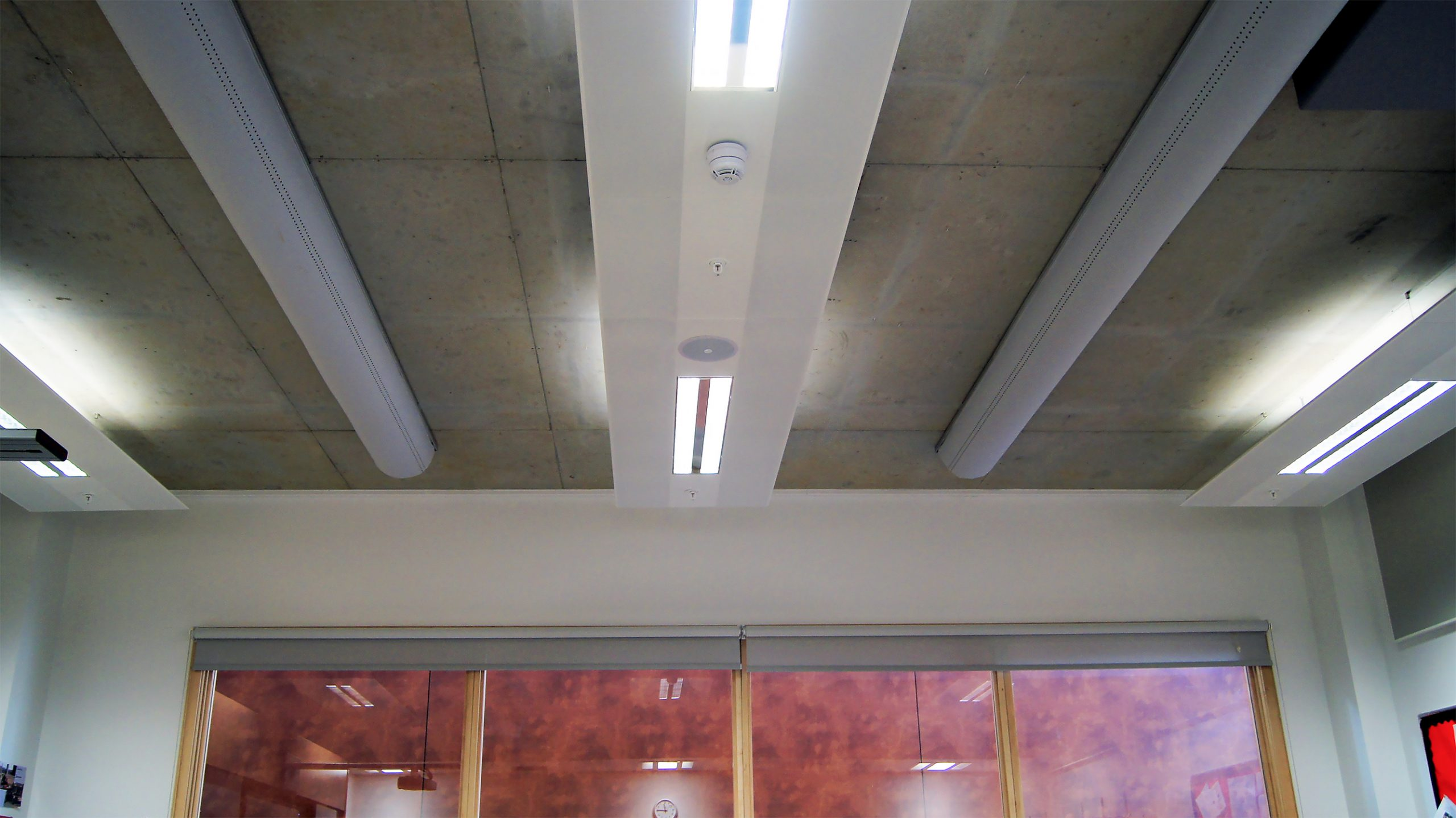 Half round fabric ducts installed on exposed concrete ceiling